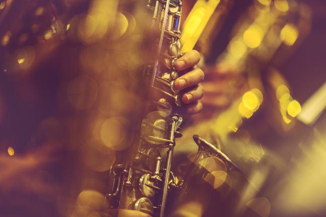 Uma foto de um saxofone, com um close-up na mão do saxofonista.