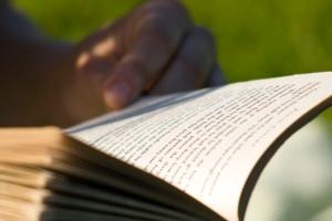 """Reading"" by Sam Greenhalgh, on Flickr, Licensed under CC BY 2.0. Close up of an open paperback book, with a hand at the edge of the page to hold it open. Green leaves and sunlight in background."