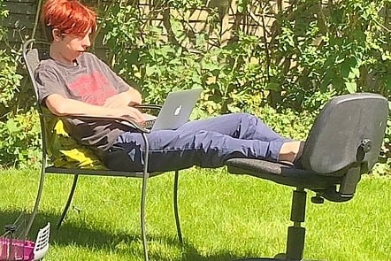 Learner using laptop in garden, sitting on garden chair with feet on office chair