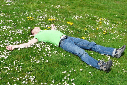 Image shows someone laid on the ground in a field looking up at the sky