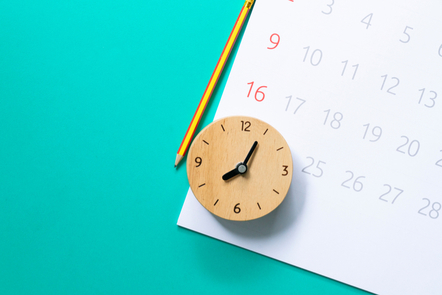 A picture of a wooden clock on a blue desk, with a small calendar.