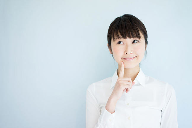 Young woman thinking against pale blue background