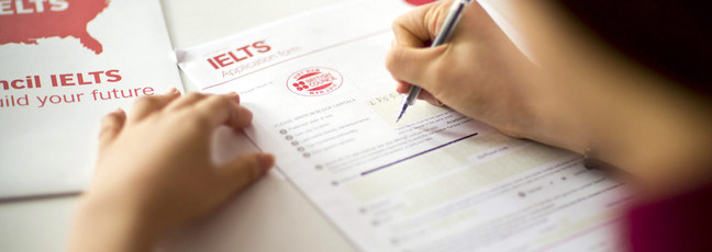 Somebody completing an IELTS application form
