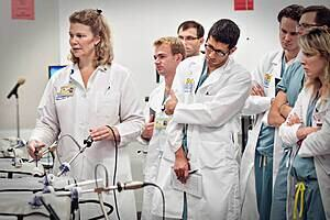 A group of medical students watching an instructor use some medical equipment