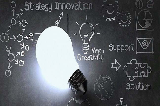 Lightbulb on chalkboard with strategy, innovation, support and solution written next to it.