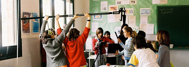 Classroom of children using film equipment to make a film