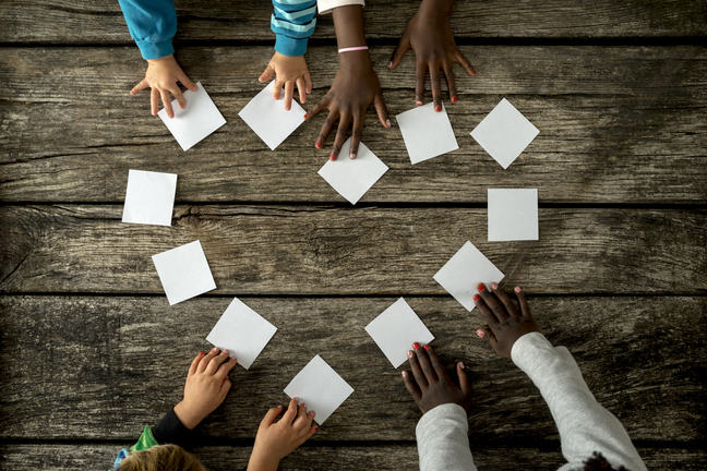 Four childrens' hands forming a love heart with white cards