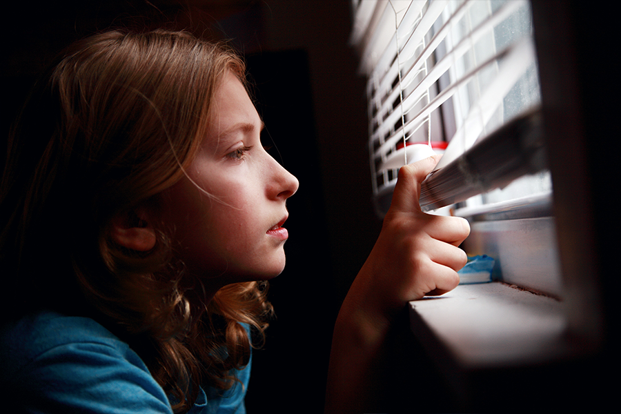 Young girl looking nervously through blinds