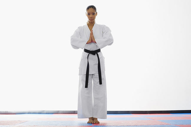 woman in white martial arts clothing with a black belt standing.