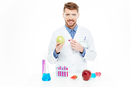 Male chemist injecting into apple isolated on a white background