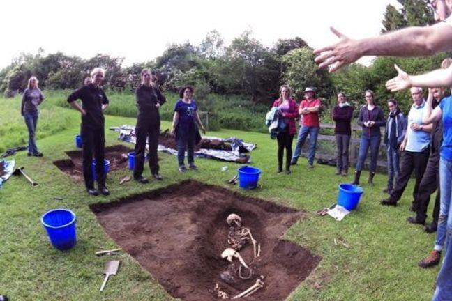 The partial excavation of a mock mass grave with students standing around it and being instructed by an educator. A skeleton is exposed within the grave.