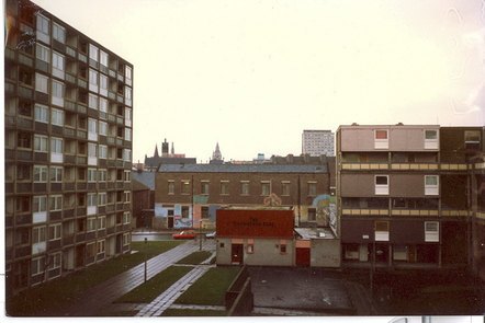 A photograph of housing the Hulme and Moss Side area of Manchester in the 1980s. On the left, there is a high rise block of flat and to the right, there is 3 story low-rise accommodation