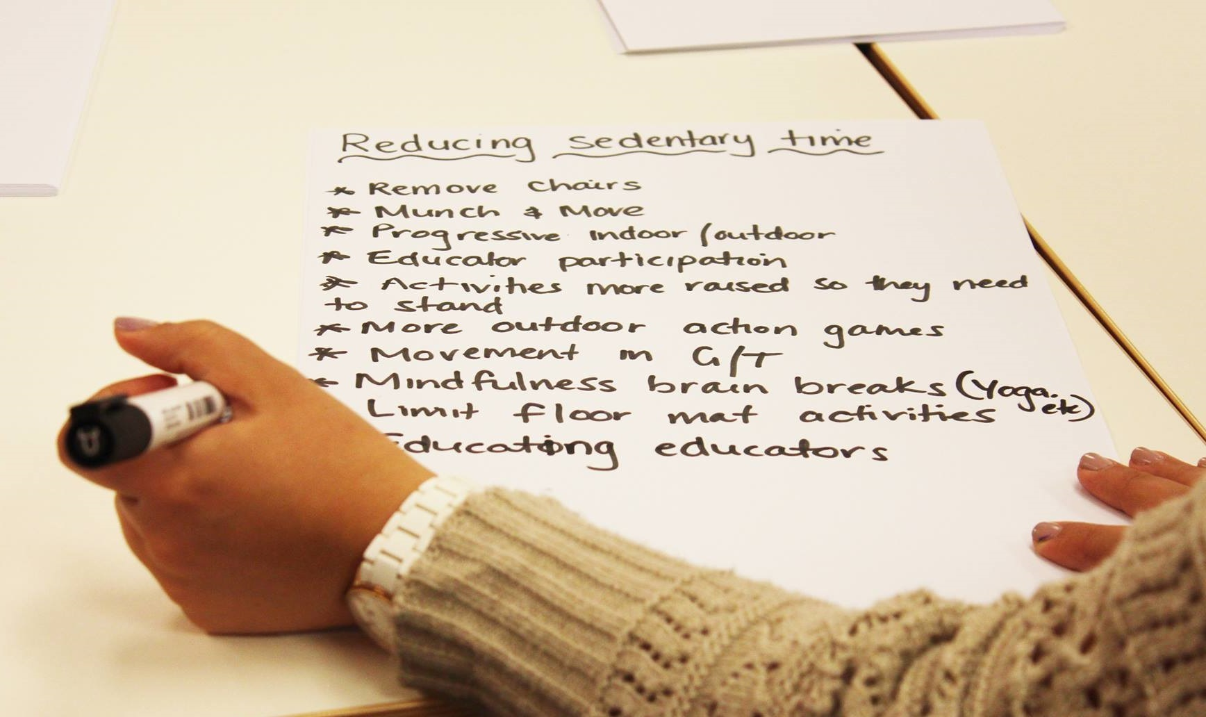 photograph of a person writing a list of strategies for reducing sedentary time and creating active spaces for children (e.g. remove chairs, munch and move, education, yoga etc.)