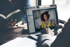 Man talking to woman on laptop via video conference.