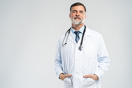 A male doctor with a stethoscope looking at the camera.