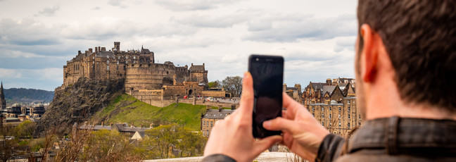 Man taking picture of Edinburgh Castle using mobile phone