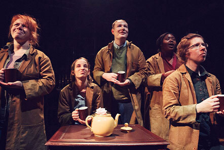 A little Space at Mind the Gap Theatre. Four women and one man are standing around a brown table with a yellow teapot on it. They are all wearing brown overcoats and holding red tea mugs. They are all looking upwards and into the distance.