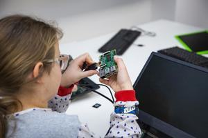 A girl plugging a HDMI cable into a Raspberry Pi