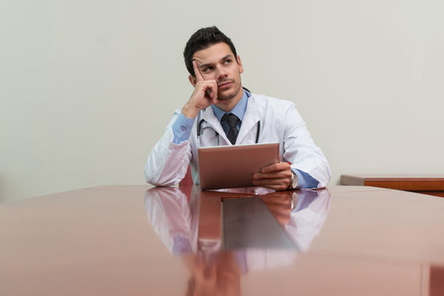 A doctor looking thoughtfully while sitting at a table with a piece of paper in his hand.