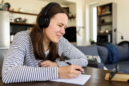 A women wearing headphones studying at home with a notebook and pen