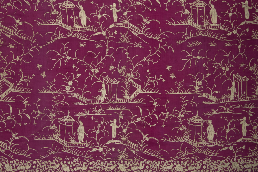 Golden embroidery on deep pink silk depicting a typical Chinese scene with a couple surrounded by pavilions and bridges.