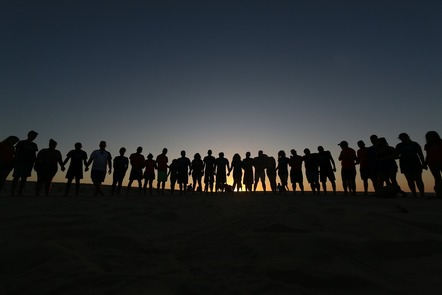 People standing in a line together on the beach