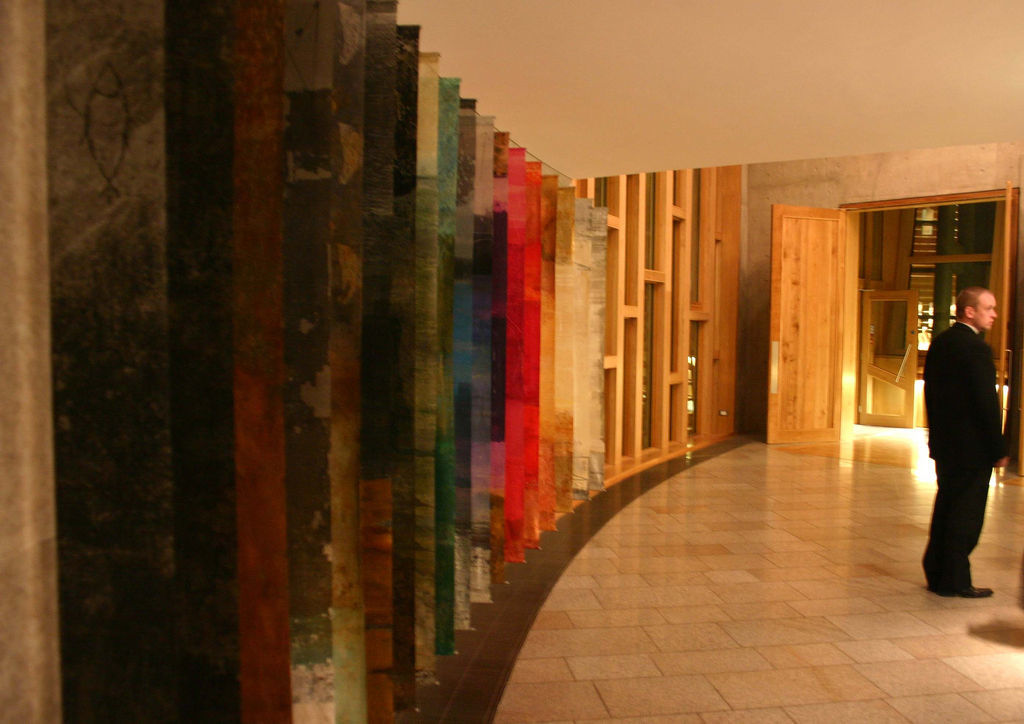 Hanging panels of colourful artwork in a corridor of the Scottish Parliament