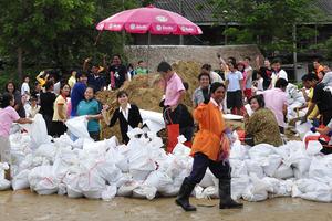 Thai community prepare for flooding by filling sandbags
