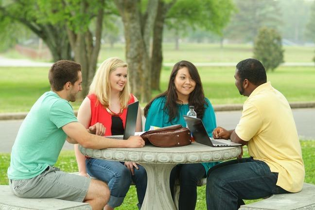 Learners seated round an outdoor table