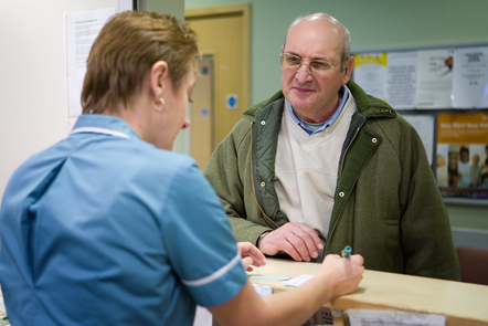 Elderly man speaking to nurse