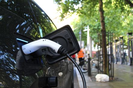 A black electric car parked on a leafy street is plugged in for charging.n