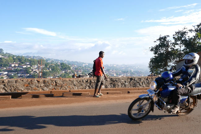 A motorbike passing a person on foot with a view over Freetown in the background