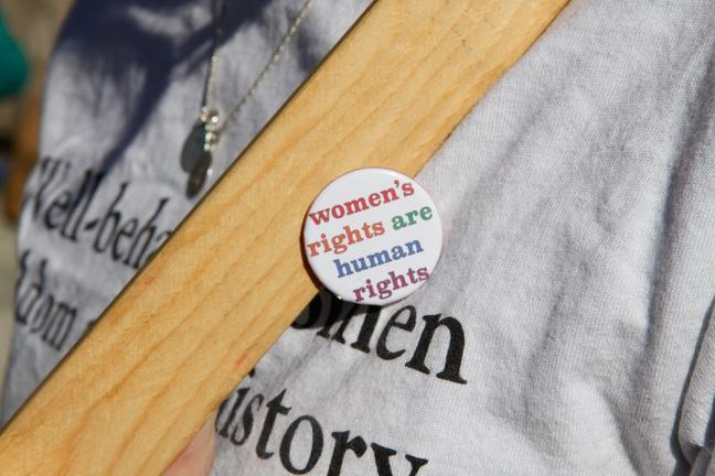 A closeup of a woman's torso, wearing a badge with the slogan 'women's rights are human rights'.