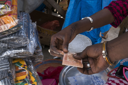A customer hands over a one thousand West African CFA franc currency banknote for goods at the Malian market