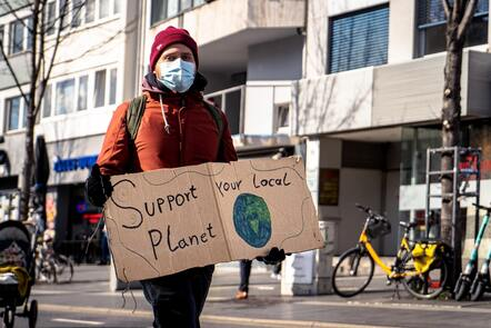 """A man in a orange park and knit cap wears a medical mask and holds up a sign that reads, """"Save Your Local Planet."""""""