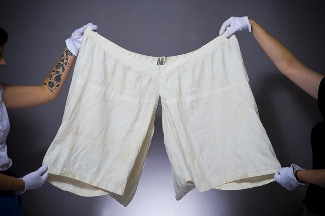 Two people holding up a pair of bloomers