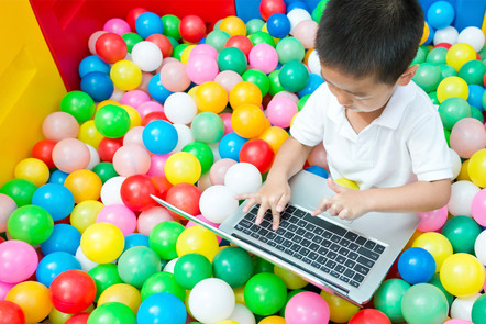 A child using a laptop in a colourful ball pool