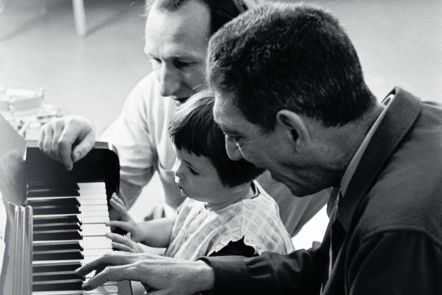 A black and white photo of Clive Robbins and Paul Nordoff and a young girl sat playing at a piano