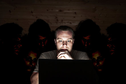 A cyber security threat - a man looks at his laptop, while people snoop over his shoulder
