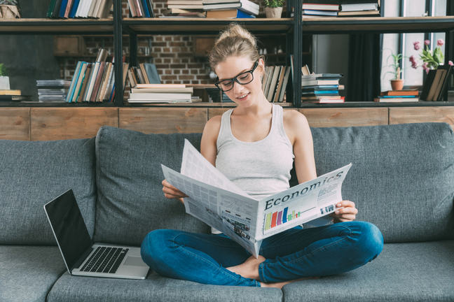 A young woman sits on the couch reading an economics newspaper