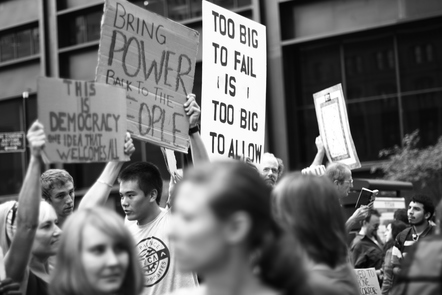 People protest at the 'Occupy Wall Street' rally, holding placards with various slogans, including 'bring power back to the people'.