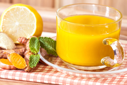 A cup of turmeric tea with lemon and ginger.