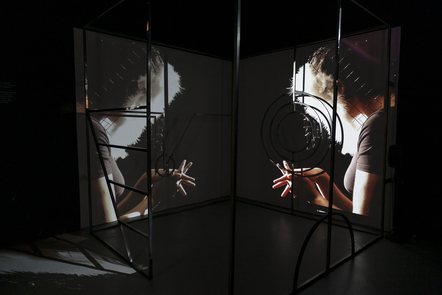Decorative image, an art installation which has two large screens surrounded by angular and circular ironwork, displaying a person with a featured mask, linking their fingers together. Emily Briselden-Waters', 2017. Circus of Anxiety.