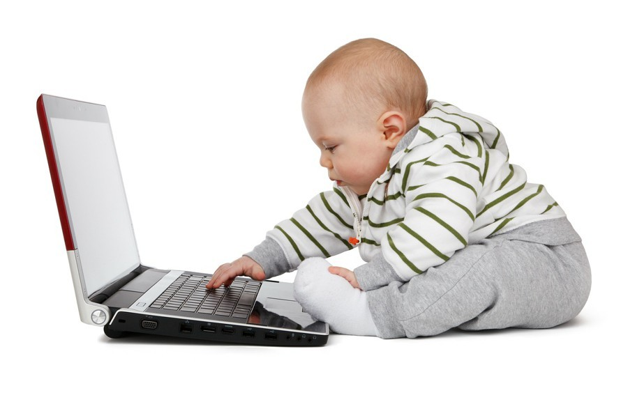 A baby playing on a laptop