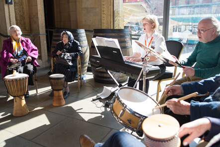 A group of elderly people are sat in a circle paying drums and shakers while a female music therapist is playing a keyboard and leading them in song