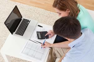 man and woman at desk with laptop, calculator and printed paper with table of numbers