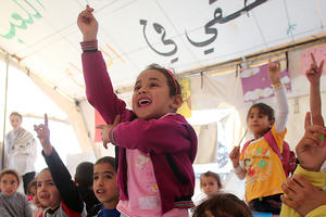 children in a makeshift classroom putting up their hands to answer a question