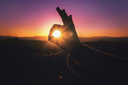 A positive hand signal with the sun in the background
