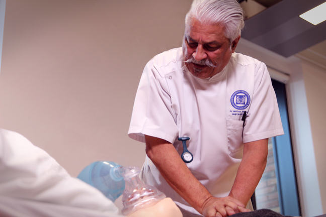 Male nurse performing a CPR on a dummy.