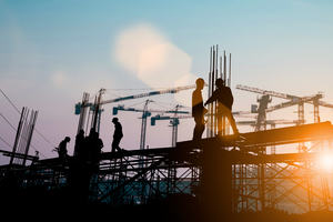 Construction workers conversing whilst standing on a steel structure